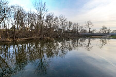 Leafless trees reflect in a mirrorlike lake on a cold winters day in Lancaster County, Pennsylvania