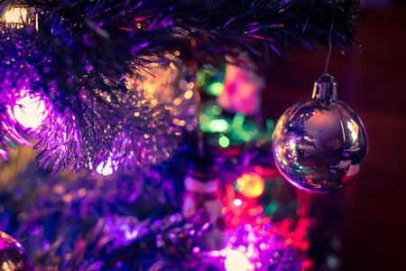 Closeup on a Christmas tree ornament surrounded by colorful lights