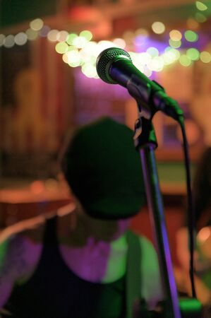 Focused on a microphone at a concert in a small venue in New York City, NYC, NY