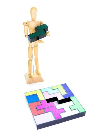 Small wooden mannequin holding the one piece needed to solve the puzzle, isolated on a white background