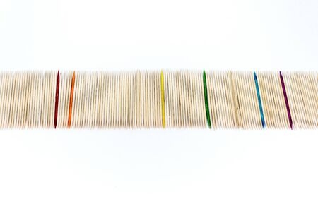 Large number of toothpicks lined up in a long row, with rainbow colored toothpicks interspersed, isolated on a white background