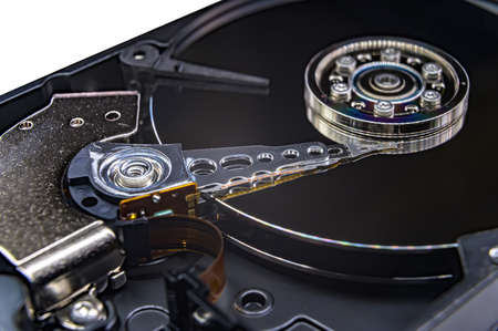 Close-up of an old fashioned, open, mechanical harddisc drive, isolated on a white background Banco de Imagens