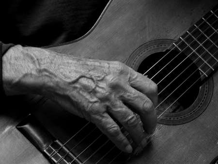 studio b: Detail of wrinkled hands of an old guitarist Stock Photo