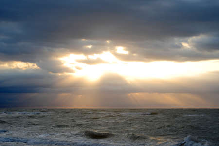 First rays of light between clouds photo