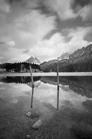 lake misurina: Reflections of poles in the water of Lake Misurina with a panorama of the Dolomites and clouds