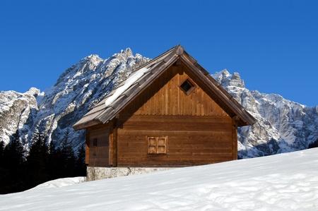 Holz-Chalet im Winter mit schneebedeckten Gipfeln - Alpen Italien