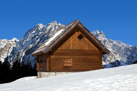 Wooden chalet in winter with snow-capped peaks - Alps Italy Stock Photo