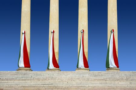 Four Italian flags of stone columns and blue sky photo