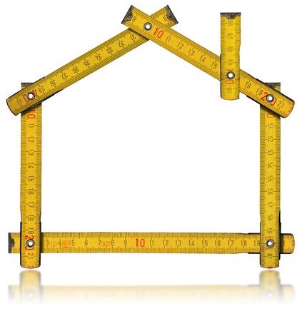 Houten gele meter hulpmiddel vorming van een huis met reflectie op witte achtergrond Stockfoto - 15470173