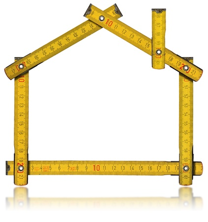Wooden yellow meter tool forming a house with reflection on white background photo