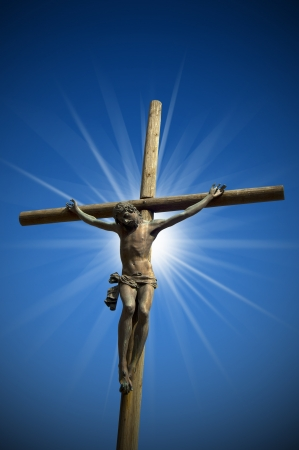 jesus statue: The cross (bronze and wood) - symbol of Gods on blue sky