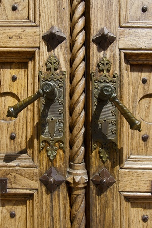Closeup of old light wooden door of a church with two bronze handles Stock Photo - 15766198