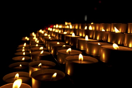 votive: A group of warm glowing candles on black background