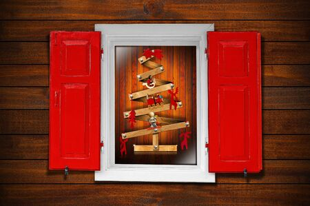 Christmas tree seen through a wooden window with red shutters photo