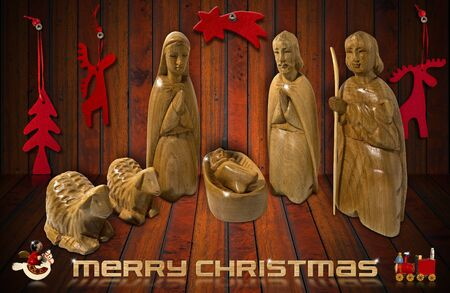Wooden Christmas Crib with Christmas objects on wooden background photo