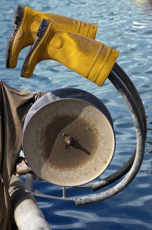 Yellow rubber boots hanging on to fishing winch - concept of fisherman's rest photo
