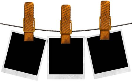 Three blank photos hanging on a steel cable with large clothespin  photo