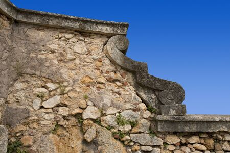confines: An old country stone wall with a ornament on blue sky Stock Photo