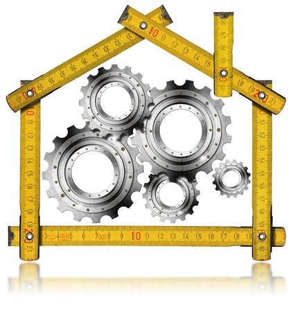 metric: Wooden yellow meter tool forming a house with metal gears Stock Photo