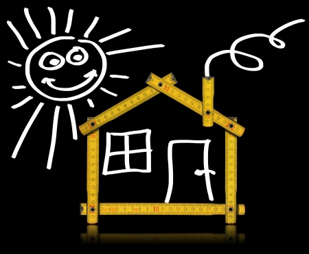 adjusted: Yellow meter tool forming a house with sun, door and window on black background Stock Photo