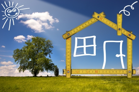ecologic: Wooden yellow meter tool forming a ecologic house in the countryside Stock Photo