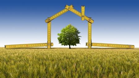 Houten gele meter hulpmiddel vormen een ecologisch huis op het platteland met boom