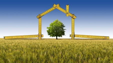 ecologic: Wooden yellow meter tool forming a ecologic house in the countryside with tree Stock Photo