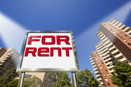 renter: Large chrome billboard with written for rent - Tall buildings in the background Stock Photo