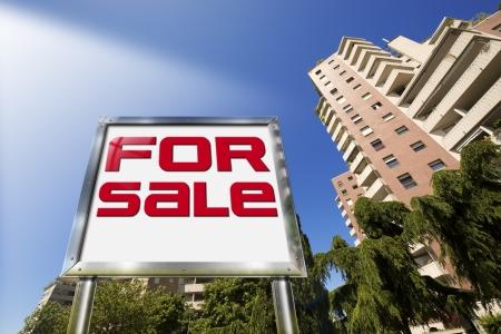 大きなクローム看板「販売」の - 記述、バック グラウンドで背の高い建物
