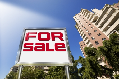 Large chrome billboard with written for sale - Tall buildings in the background