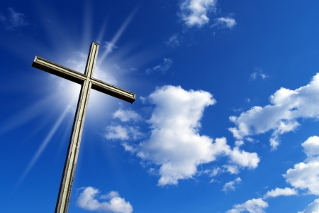 Wooden high cross with blue sky, clouds and reflection