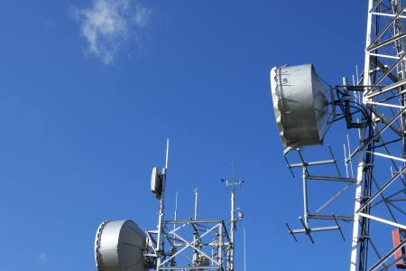 Two communication towers with a beautiful blue sky photo