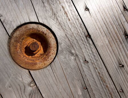 Background with wooden boards of pine, round rusty plaque and bolt photo