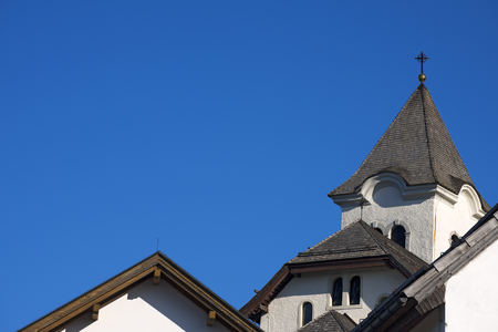 Ancient roofs of mountain sanctuary against blue sky background - Lussari Italy photo