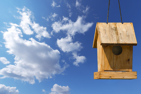 crafted: Old wooden birdhouse on a blue sky with free space for text