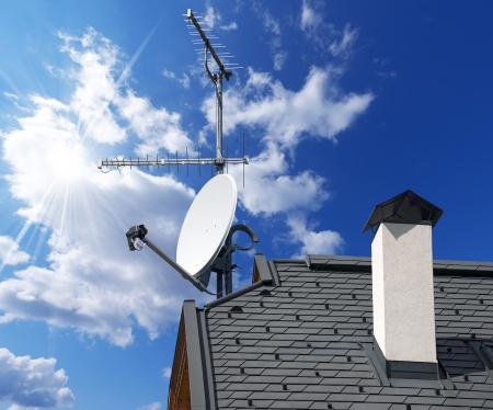 Schotelantenne en TV-antennes op het dak van het huis met een mooie blauwe hemel