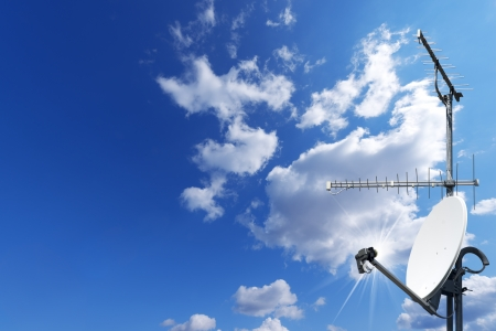 One satellite dish and two TV antennas with a beautiful blue sky Archivio Fotografico