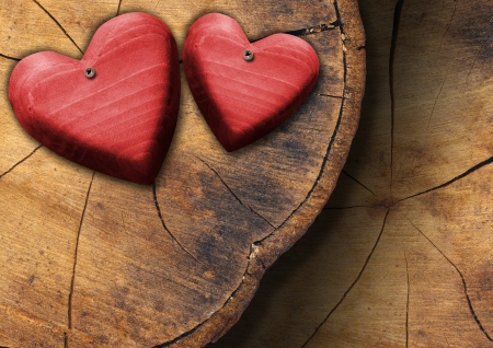 Two handmade red wooden hearts hanging on wooden background with trunk section Archivio Fotografico
