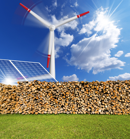 Solar panels, firewood logs in a pile and a turbine power station - renewable energy photo