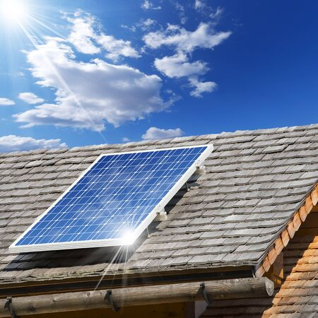 shingles: Old roof with wooden shingles and solar panel with reflection of blue sky Stock Photo