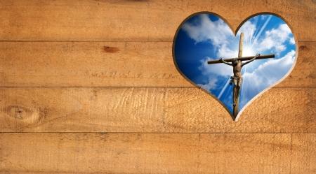 Houten muur met een gat in de vorm van hart met Jezus gekruisigd en blauwe hemel met wolken