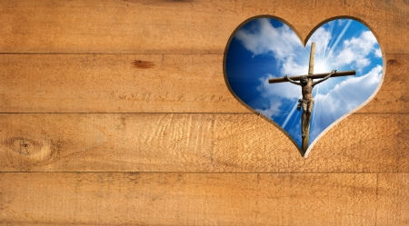 Wooden wall with a hole in the shape of heart with Jesus crucified and blue sky with clouds