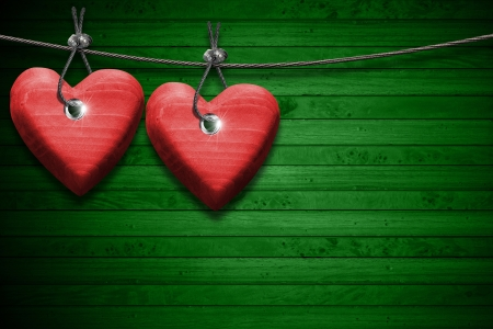 Two handmade red wooden hearts hanging on a steel cable on green wooden background Stock Photo - 23017166