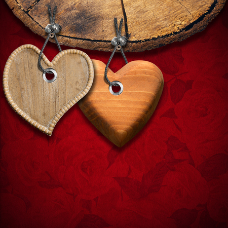 Two wooden hearts hanging from a section of tree trunk on red velvet with roses flowers photo