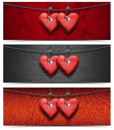 Two handmade red wooden hearts hanging on a steel cable on fabric   photo