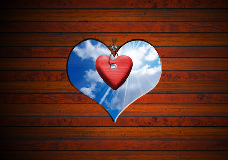 Brown wooden wall with a hole in the shape of heart with blue sky and red heart photo