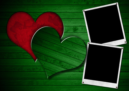 Two instant photo frames on green wooden wall with a hole in the shape of heart and red velvet background with roses flowers photo