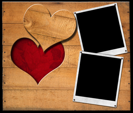 Two instant photo frames on brown wooden wall with a hole in the shape of heart and red velvet background with roses flowers Stock Photo - 23237020