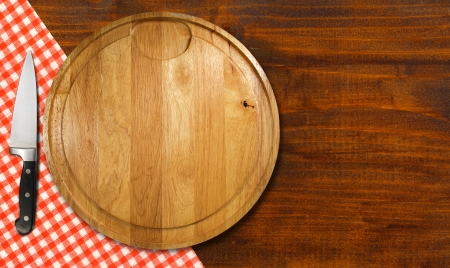 Round cutting board with red checked tablecloth and kitchen knife on brown wooden table photo