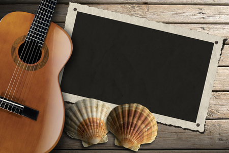 Acoustic brown guitar and aged photo frame with two sea shells on beach wooden floor over summer sand photo